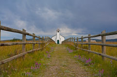 Country Church. Small white country church with fence and stormy clouds Stock Photography