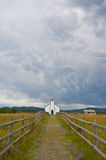 Country Church. Small white country church with fence and stormy clouds Royalty Free Stock Image