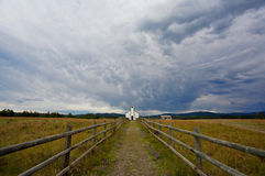 Country Church. Small white country church with fence and stormy clouds Royalty Free Stock Photos