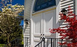 Country church door in spring. Closeup of a white country church door in spring Royalty Free Stock Photography