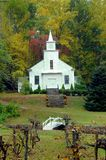 Country Church with Grape Arbor. Old country church has small white bridge and grape arbor.  Fall foilage fills background Royalty Free Stock Photo
