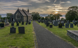 Country church and graveyard at sunset Stock Image