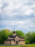 Country church near the park. Small orthodox church near the park under the beautiful sky with clouds Stock Photo