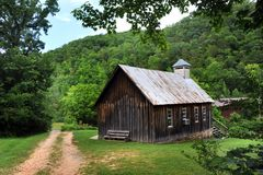 Ozark Church by Dirt Road. Country church in the Ozark Mountains of Arkansas sits on grassy foothill with gravel road running besides it Stock Photos