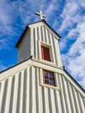 Country Church Steeple, Iceland. Low-angle view of steeple and cross on a small country church in Iceland Stock Photo