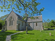 Country church on a sunny day. Country church in a churchyard with old tombstones Royalty Free Stock Images