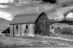 Country cloudscape. An old wooden barn surrounded by hay fields in the hills of Eastern Washington Royalty Free Stock Photo