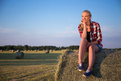 Country concept - beautiful dreaming woman sitting on haystack i Stock Photography