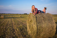 Country concept - beautiful romantic woman lying on haystack in Royalty Free Stock Photography