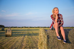 Country concept - beautiful woman sitting on haystack in field Stock Photography