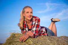 Country concept - girl lying on haystack over blue sky Royalty Free Stock Image