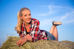 Country concept - young woman lying on haystack over blue sky Stock Images