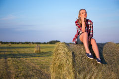 Country concept - young woman sitting on haystack in field Royalty Free Stock Photos