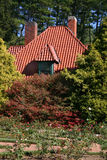 Country Cottage in Formal Garden. Quaint country cottage surrounded by shrubbery in a formal garden Stock Photo