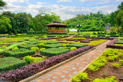 Country cottage garden path, Thai style pavilion is located in the middle with tree background. stock photo