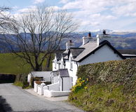 Country Cottage. A country cottage in Wales, situated on the side of a steep lane with snow-capped hills in the background stock images
