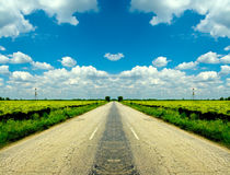 Country cracked road and blue cloudy sky. Country road stretching out into the horizon Royalty Free Stock Photo