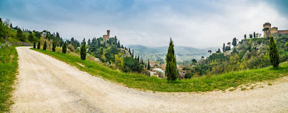 Country dirt road bordered by cypress trees. Next to the clock tower of the village of Brisighella in Italy Stock Images