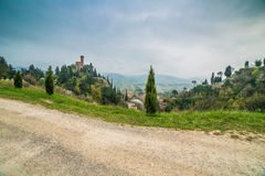 Country dirt road bordered by cypress trees. Next to the clock tower of the village of Brisighella in Italy Royalty Free Stock Photos