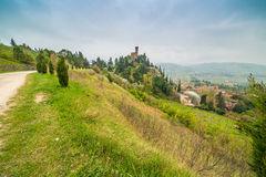 Country dirt road bordered by cypress trees. Next to the clock tower of the village of Brisighella in Italy Stock Photo