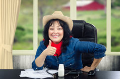 Country doctor gives thumb up looking at camera. Country female doctor gives thumb up and looks at camera. Black haired mature woman wears jeans shirt and yellow Royalty Free Stock Photography