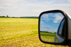 Country drive. Beautiful country field with blue sky in the side view mirror. Focus on mirror Stock Photo