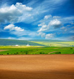 Country dry plowed earth agricultural green farmland on blue sky royalty free stock photography