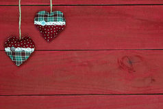 Country fabric Christmas hearts hanging from rope against antique red wood background Royalty Free Stock Image