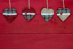Country fabric Christmas hearts hanging from rope on antique red rustic wood background Stock Photography