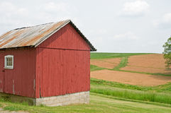 Country farm building and field. A closeup view of an old country farm building with planted fields in the background Stock Images