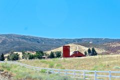 Country farm. Red barn on hillside of Country landscape in Lancaster California Stock Photos