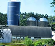 Country Farm. This is rural farm setting on a farm that milks cows for selling with structures called silos that holds grain for the livestock Stock Photo