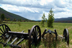 Country farm vehicles. Landscape view of high country ranch farm vehicles sitting in a mountain meadow Royalty Free Stock Photography