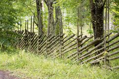 Country fence in perspective. Covered in green lichen and surrounded by trees Stock Photo