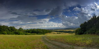 Country field panorama. A panoramic, landscape view across an open green field with light, fluffy, summertime clouds Royalty Free Stock Photos