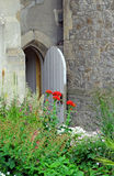 Country garden arch door. Photo of a country garden arch doorway in castle wall surrounded by summer flowers and plants Stock Photography