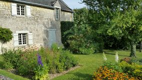 Stone house and Country garden scene. Stone cottage with green lawn, trees and colourful flowers in sunshine Stock Images