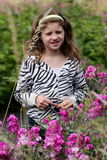 Country Girl. A young country girl standing in wild flowers wearing zebra jacket. Shallow depth of field Stock Image