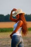Country girl. Girl with long hair and cowboy hat looks into the camera near sunset with farm land and young cornfield in background
