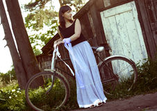 Woman with bicycle near old house Royalty Free Stock Photography