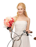 Country girl with bicycle and flowers Stock Images