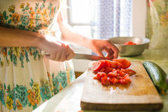 Country girl is cutting vegetables for salad in the kitchen, cooking dinner. village house, natural light.  Royalty Free Stock Images