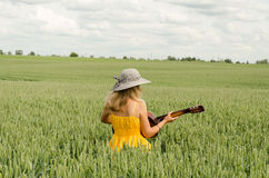 Country girl in dress play guitar wheat field Stock Photos