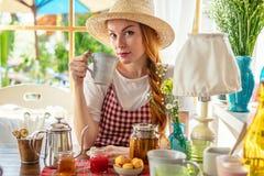 Country girl drinking tea. Tea pot, homemade honey, jam, muffins on table