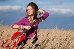 Country girl fixing her hair and holding an acoustic guitar in field against blue cloudy sky background Royalty Free Stock Image