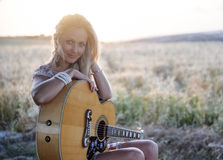 Country girl and guitar 2. A country girl and her guitar sitting on a bench in a hay field with her hat next to her 2 Royalty Free Stock Photos