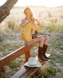 Country girl and guitar. A country girl and her guitar sitting on a bench in a hay field with her hat next to her Royalty Free Stock Images