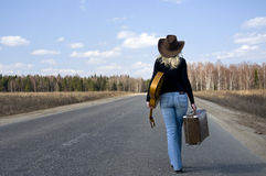 Country girl with guitar goes on road solitary Stock Photos