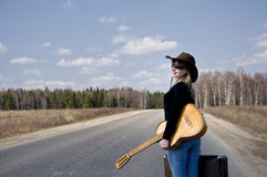 Country girl with guitar goes on road solitary Stock Image