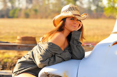 Country girl with hat. Tan country girl in open shirt and blue jean cut off shorts, wagon wheel and field in background, leaning against an old truck at sunset Royalty Free Stock Photography